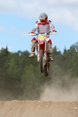 Cyclist wearing in helmet on dirt motorcycle jumps