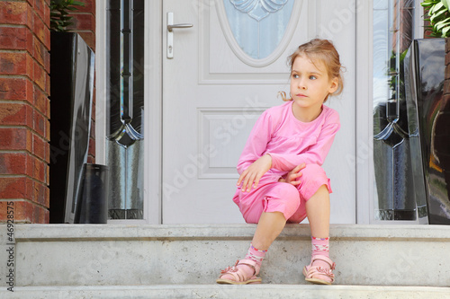 Little awake girl sits on stairs near door and looks away.
