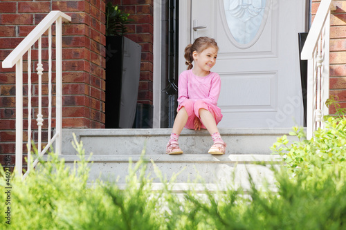 Happy girl sits on stairs near white door, smiles and looks away