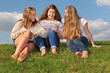 Three girls sit at green grass, chat and laugh at sunny day.
