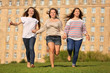 Three smiling girls run at green grass and hold hands
