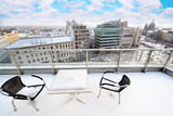 Table and chairs on balcony in snow at winter.