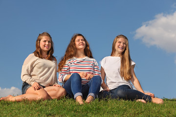 Three barefoot girls sit at green grass and look into distance