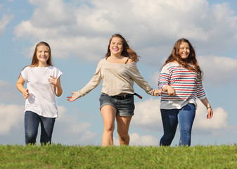 Three girls run at green grass and smile at background of sky