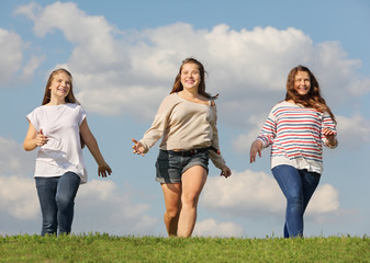 Three smiling girls run at green grass at background of blue sky