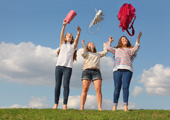 Three girls throw up bags and stand at green grass