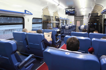Back of passengers sitting in soft chairs in train carriage