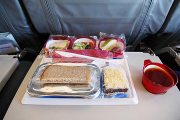One serving on tray of packed food at airplane. Focus on bread.
