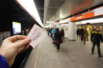 Male hand holds two tickets in subway. People wait for train
