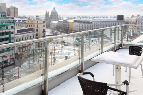 Table and chairs on balcony in snow at winter day. View of city.