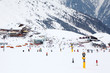 Many skiers ride at mountain. Cable car, hotels in Alps