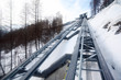 Metal tracks for mountain lift and winter forest in mountain.
