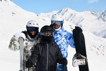 Happy family in sport suits and helmets stand with snowboard