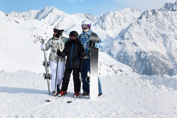 Family in helmets stand with snowboard and skis on mountain