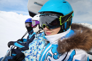 Three skiers in special clothing and helmets ride on cable car