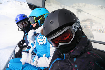 Three skiers in helmets and goggles ride on funicular