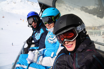 Three happy skiers in helmets and goggles ride on funicular