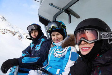 Three happy skiers in helmets and sport suits ride on funicular