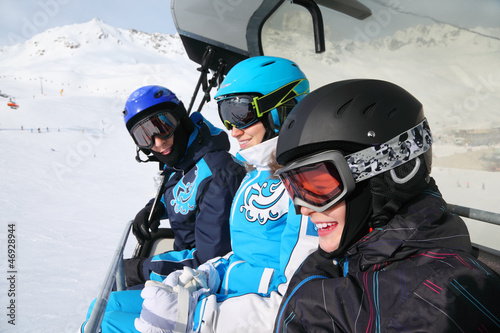 smiling skiers in helmets and goggles ride on funicular
