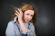 Brown-haired woman hold hair fluttering in wind in photo studio