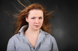 Brown hair woman with hair fluttering in wind in photo studio