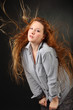 woman pose in shirt with hair fluttering in wind in photo studio