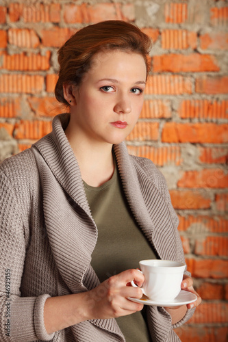 brown-haired woman hold cup, plate near brick wall, half body