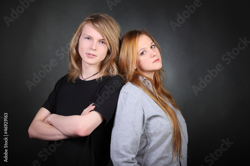 Long hair boy and brown hair girl lean pose in photo studio