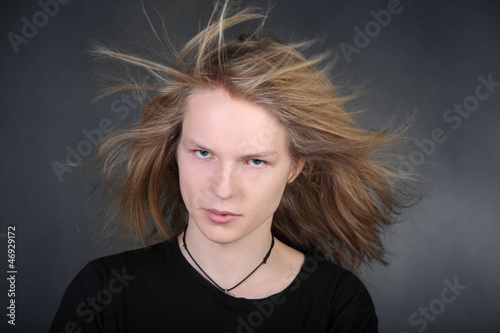 Long hair boy with streaming hair in photo studio