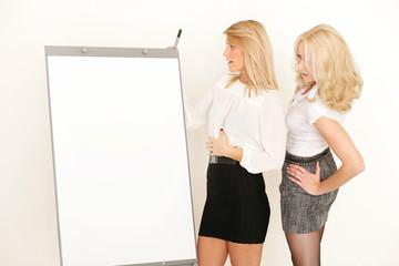 Zwei Blondine vor einem Flipchart