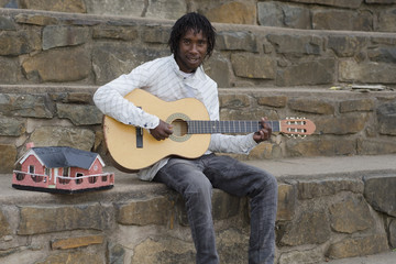 African busker on stone stairs