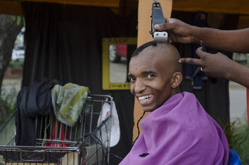 Smiling customer at African small haircut barber business