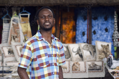 african curio salesman vendor  in front of ethnic wildlife items