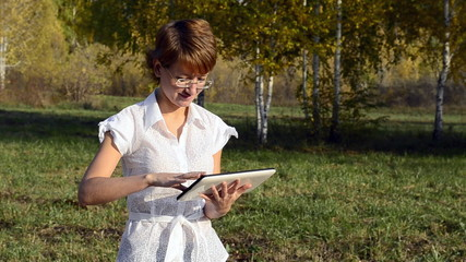 Young woman running on a Tablet PC in the autumn park