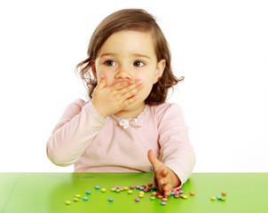 Ein Mädchen isst bunte Smarties