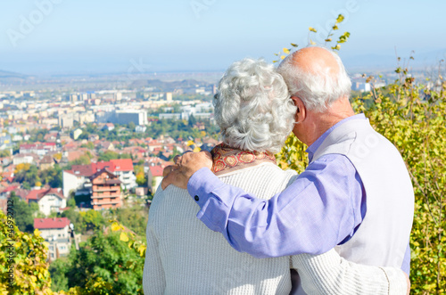 Beautiful senior couple looking to the city