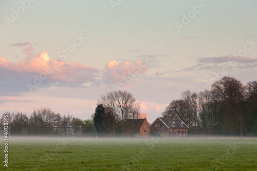 Meadow with house in the mist at sunset. Cloudy sky.