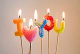 Colorful burning candles making 'I love you'