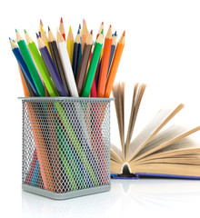 colored pencils and a book on a white background