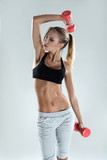 Slim and sporty girl do exercise with dumbbells
