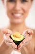 Beautiful woman portrait with fresh avocado in hand