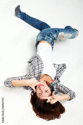 Attractive woman making frame with her hands lying on a floor