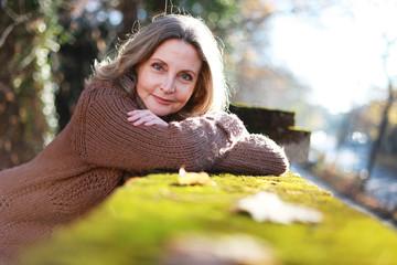 Schöne ältere Frau entspannt bei einem Herbstspaziergang