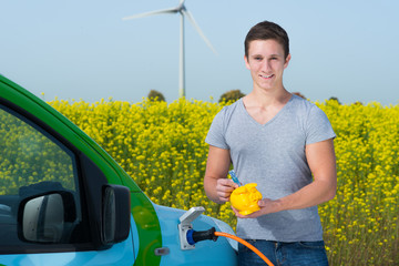 junger mann spart mit einem elektroauto