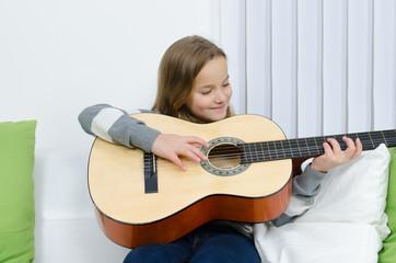 schülerin lernt gitarre spielen