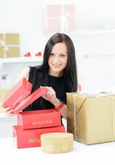 attraktive junge frau öffnet weihnachtsgeschenke