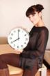 Attraktive Brünette präsentiert die Uhrzeit