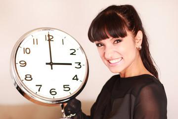 Attraktive junge Frau hält eine Wanduhr in der Hand
