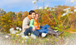Sweet couple sitting on a hill  at the autumn landscape