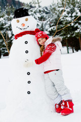 Winter - lovely girl is making snowman